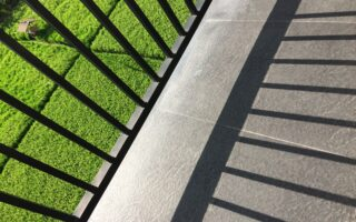 A metal fence shadow on the balcony with a view of a grassy field on a sunny day